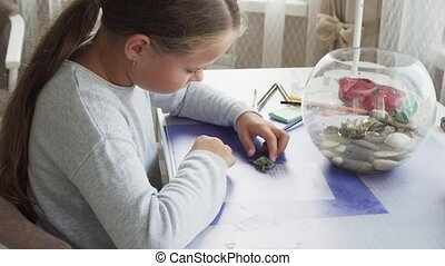 Little girl playing with domestic turtle on table at home