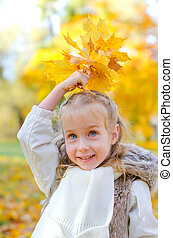 Little girl playing with fallen autumn leaves.