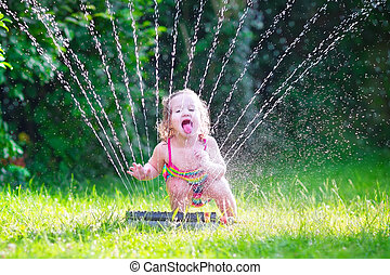 Little girl playing with garden sprinkler - Funny laughing...
