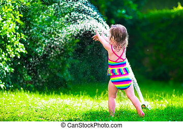 Little girl playing with garden water sprinkler