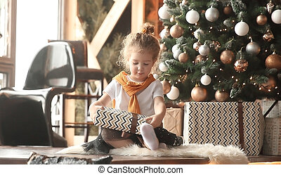 little girl playing with gifts near the Christmas tree