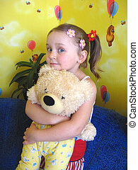 girl playing with her bear toy in her room