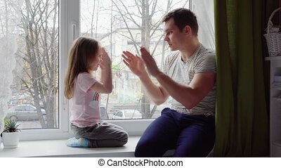 Little girl playing with her father at okay