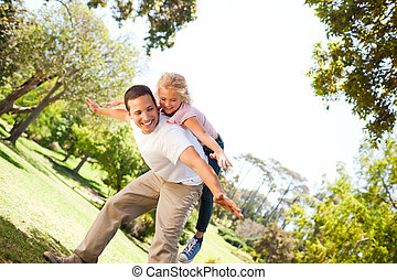 Little girl playing with her father in the park