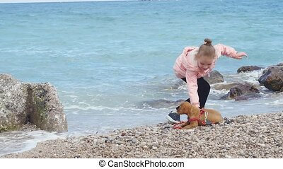 Little girl playing with her puppy near the sea