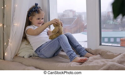 Little girl playing with her toy bear and sitting on window sill