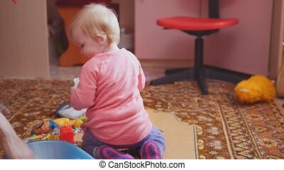 Little girl playing with her toys, mom helping, family and...