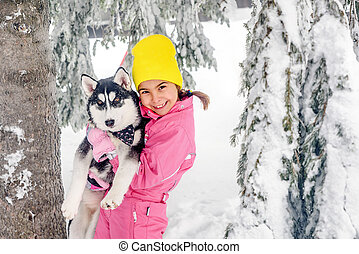 Little girl  playing with Husky dog on the snow