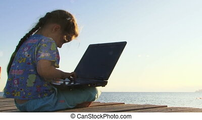 Little Girl Playing with Laptop Near Sea