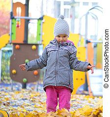 little girl playing with leaves in autumn