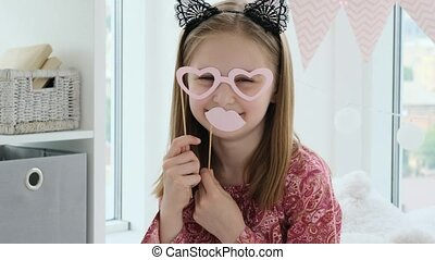 Nice little girl playing with lips and glasses on stick in kids room