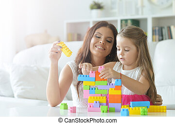 little girl playing with mother