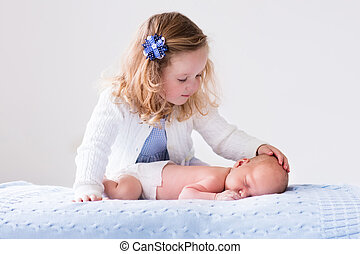 Little girl playing with newborn baby brother - Little...