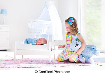Little girl playing with newborn baby brother