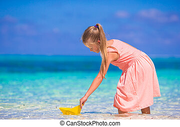 Little girl playing with origami boat in turquoise sea