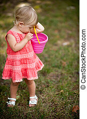 little girl playing with pail