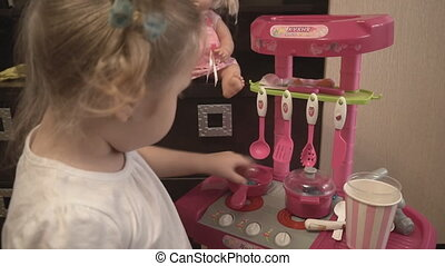 Little girl playing with pink toy kitchen