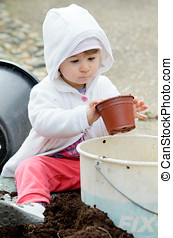 Little girl playing with plant pot