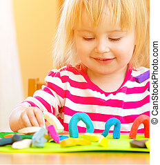 Little girl playing with plasticine