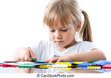 Little girl playing with puzzle pieces.