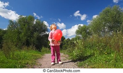 little girl playing with red balloon in park, ballon has burst