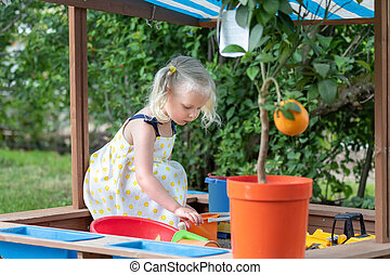 Little girl playing with sand in a sandbox