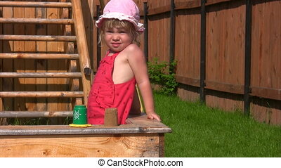 little girl playing with sand mould in sandbox outdoor