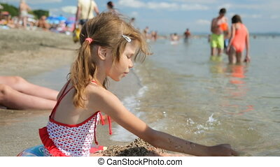 Little girl playing with sand on beach