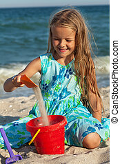 Little girl playing with sand on the beach