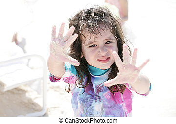 Little girl playing with sand.