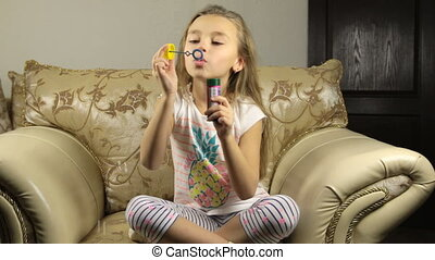 Little girl playing with soap bubbles at home in bright living room
