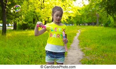 Little girl playing with soap bubbles in summer park - Cute...