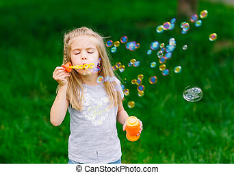 Little girl playing with soap bubbles in the park
