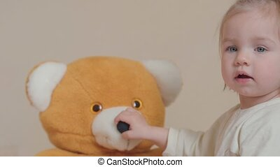 little girl playing with Teddy bear at home