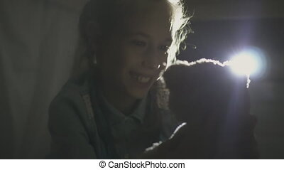 Little girl playing with teddy bear in tent under the table.