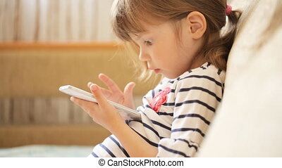 Little girl playing with the smartphone