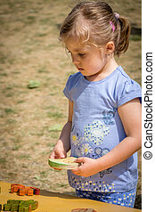Little girl playing with the wooden puzzle