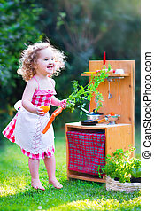Adorable curly toddler girl wearing a red dress and white lace apron having fun playing with a toy doll kitchen in a sunny summer garden with healthy vegetables and herbs