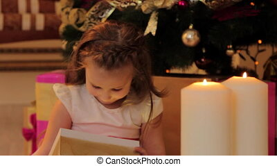 Little Girl Playing with Toys by Christmas Tree