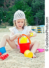 Little girl playing with toys on the beach