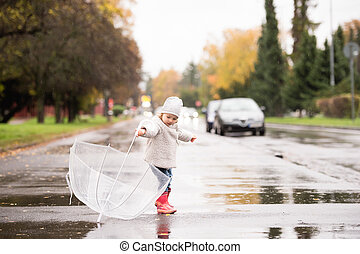 Little girl playing with transparent umbrella outside, rainy...