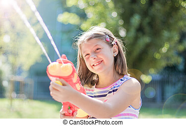 little girl playing with water gun in the park on a sunny day