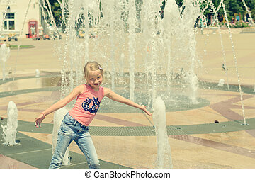 Little girl playing with water in city fountain.