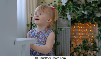 Little girl playing with white wooden rocking horse