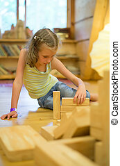 Little girl playing with wooden blocks.