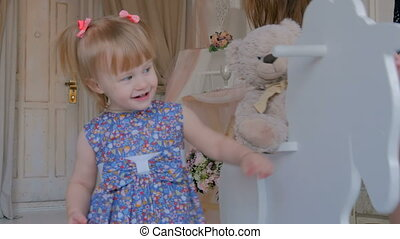 Little girl playing with wooden rocking horse - Little girl...