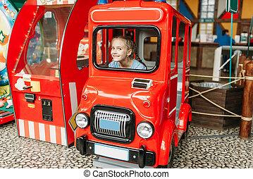 Little girl plays a bus driver, game machine, children...