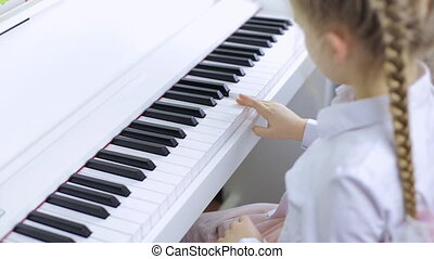 Little girl plays classical music on a piano