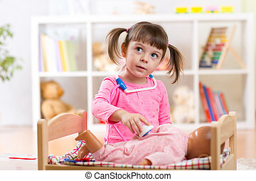 Little girl plays doctor examining a doll patient with toy stethoscope