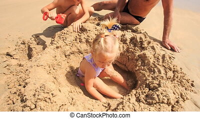 Little Girl Plays in Sand Hole by Grandpa Boy on Beach